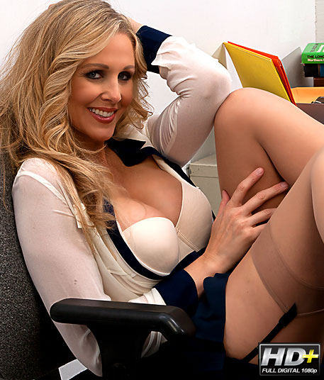 blonde bombshell sitting at her desk with her big breast exposed